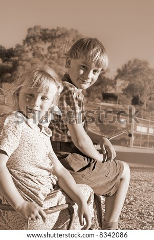 young boy rides off with a girl in the back of the old tricycle - stock photo