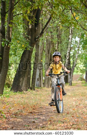 Young boy riding bicycle in a park - stock photo