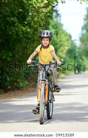 Young boy riding bicycle on a summer day - stock photo