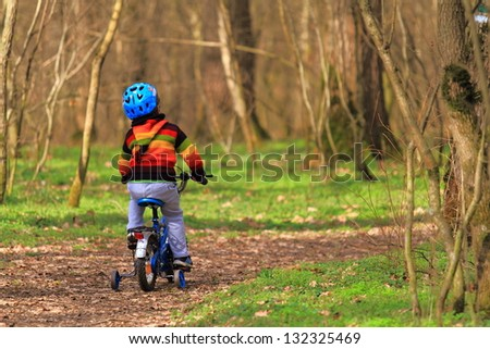 Young boy riding his bike on the forest trail - stock photo