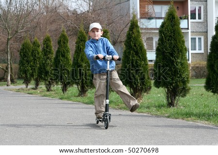 Young boy riding two wheeled scooter.