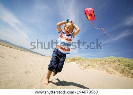 Young boy running and laughing flying a kite on the beach on his summer vacation - stock photo