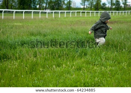 Young boy running around in grass filed