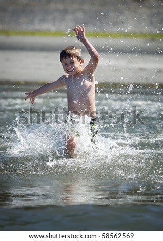 young boy running into the ocean - stock photo