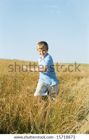 Young boy running outdoors smiling - stock photo