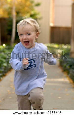 Young boy running, smiling - stock photo