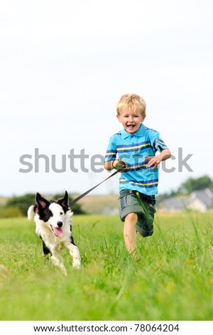 Young boy runs in a green field with his pet collie - stock photo