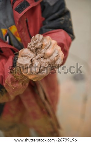 Young boy's hands squeezing clay/mud. - stock photo