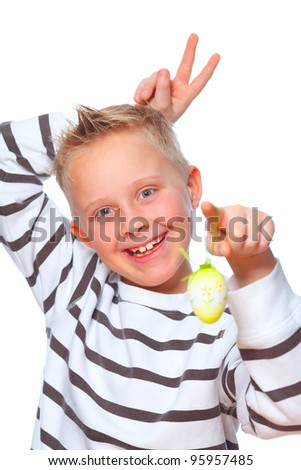 young boy showing easter egg and making rabbit ears behind his head