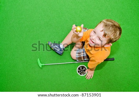 Young boy showing off golf ball after pulling it out of hole while playing miniature golf - stock photo