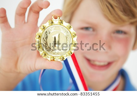 Young boy showing off medal - stock photo