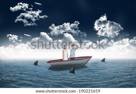 Young boy showing something to his sister against sharks circling small boat in the sea - stock photo