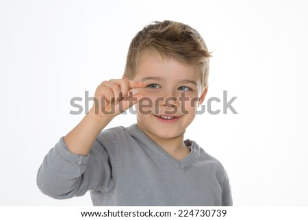 young boy shows a very little measure - stock photo