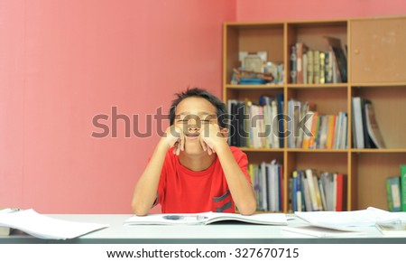 young boy shows bored face during studying  - stock photo