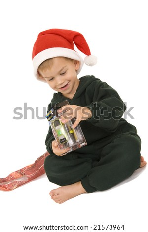 Young boy sitting in Santa hat with new toy. Isolated on white.