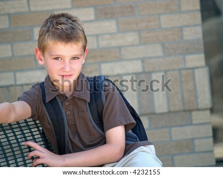 young boy sitting on a bench and waiting for the school bus