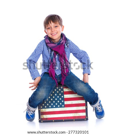 Young boy sitting on a case, american style, isolated on white - stock photo