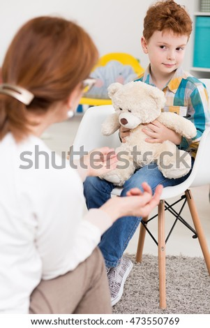 Young boy sitting on a chair with a teddy bear in his hands