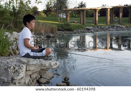 Young boy sitting on a rock while fishing - stock photo