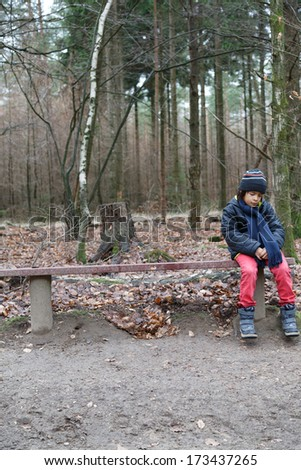 Young boy sitting on a rustic wooden bench in woodland staring down at the ground as he waits for someone - stock photo