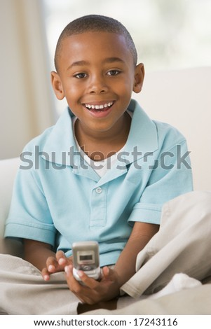 Young Boy Sitting On A Sofa, Text Messaging - stock photo