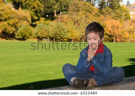 young boy sitting on a wood bench in a park praying or meditating - stock photo