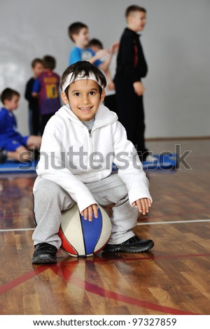 Young boy sitting on basketball, his friends in background - stock photo