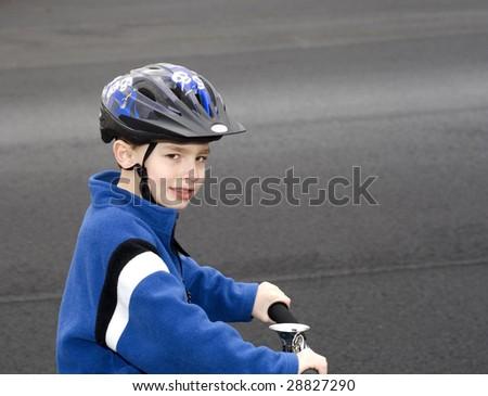 Young boy sitting on bike wearing helmet smiling - stock photo
