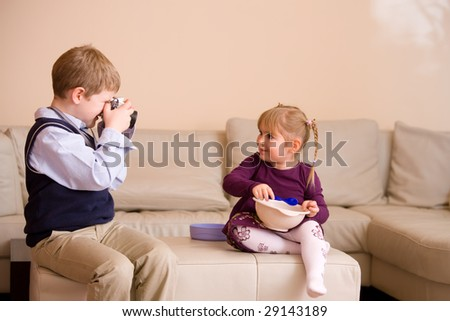 Young boy sitting on couch, taking a picture of his happy little sister, - stock photo