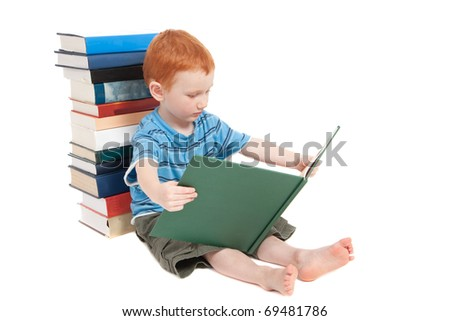 Young boy sitting on floor, leaning against pile of books, and reading