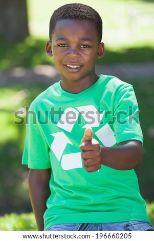 Young boy sitting on grass in recycling tshirt showing thumb up on a sunny day - stock photo