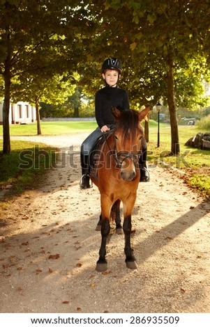 Young boy sitting on horseback in the nature. - stock photo