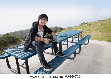young boy sitting on picnic table with tablet PC smiling