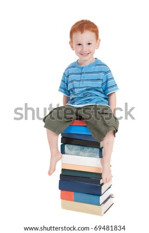Young boy sitting on stack of books. Isolated on white. - stock photo