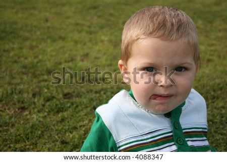 Young boy sitting on the grass with a frown - stock photo
