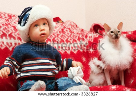 young boy sitting on the red cover with cat dressed like Santa Claus - stock photo