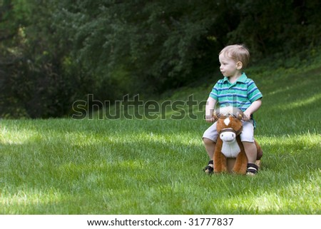 Young boy sitting on toy horse outside - stock photo