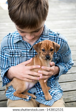 Young Boy Sitting Outside Holding his Puppy on Lap - stock photo