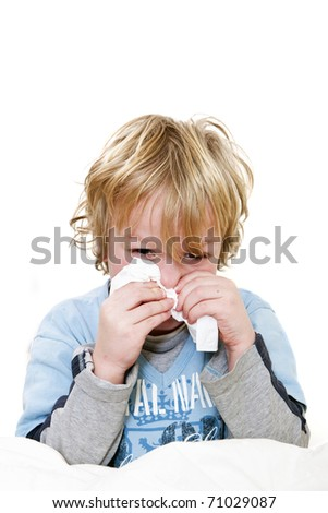Young boy sitting straight up in his bed, sneezing, with a handkerchief in his hands, and a red head and a tear in his eye from the effort and fever - stock photo