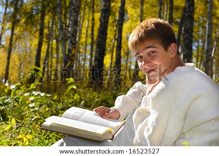 young boy sitting with a book - stock photo