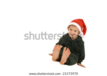 Young boy sitting with Christmas hat on and his feet out in front of him. Isolated on white.