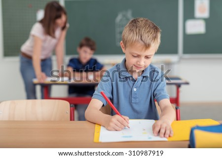 Young boy sitting writing notes at school seated at his desk in the classroom with is teacher helping a second student in the background - stock photo