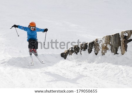 Young boy ski jumping in the snow - stock photo