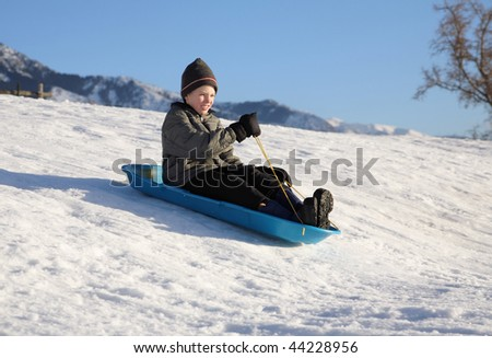 young boy sledding down a snowy hill on a blue sled - stock photo