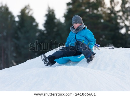 Young boy sledging downhill om a blue sledge on a winter day - stock photo
