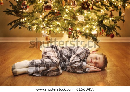Young boy sleeping under the Christmas Tree waiting for Santa Claus to come - stock photo