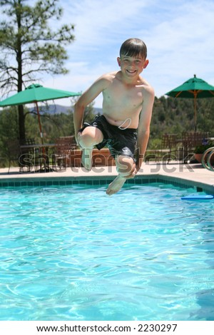 Young boy smiling and jumping into a swimming pool - stock photo