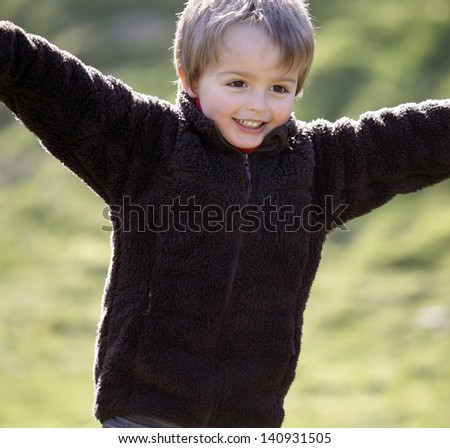 Young boy smiling and running with arms outstretched outdoors - stock photo