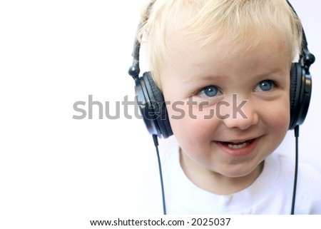 Young boy smiling and wearing headphones - stock photo