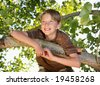 young boy smiling in a tree - stock photo